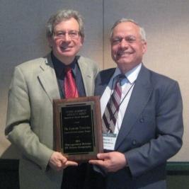 Carlos Teixeira receives the Scholar Award from Stavros Constantinou.